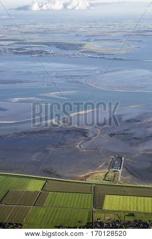 Aerial coastal view of the shore of Ameland Frisian Island with green fields dike and sea The Netherlands