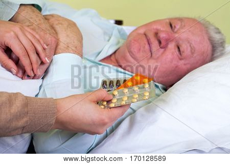 Picture of a sick elderly man with his carer holding medication