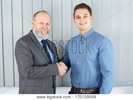 Picture of a senior employer making an agreement with a young entrepreneur
