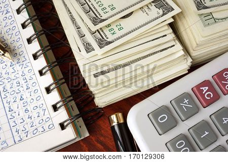 Ledger book, pack of dollar bills and calculator. Home finance concept.