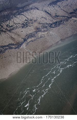 aerial view of estuary mudflat wetland of the shore of World heritage Unesco site Ameland island with sea and waves. The Netherlands