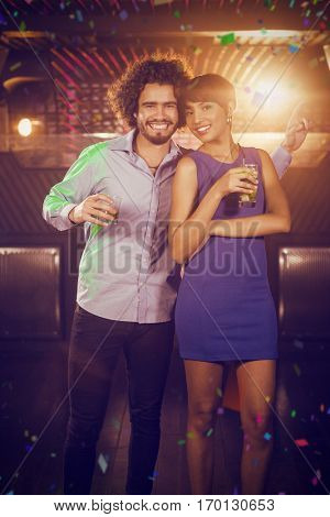 Cute couple dancing together on dance floor while having drink against flying colours