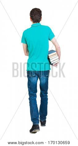 Back view of going  handsome man carries a stack of books.   backside view of person.  Isolated over white background. Sad man in a green T-shirt goes deep into the frame with a stack of books.
