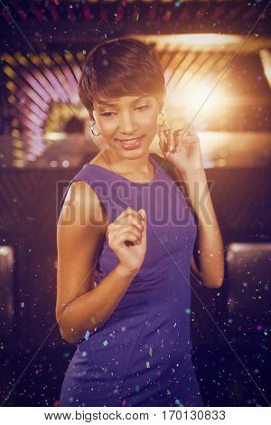 Young woman dancing on dance floor against flying colours