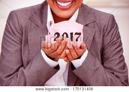 Close up of a smiling businesswoman holding a piggybank against digital image of new year 2017