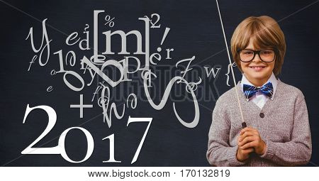Portrait of smiling boy with stick standing next to happy new year wishes on blackboard