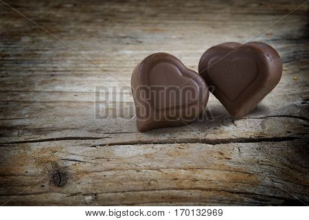 Two chocolate hearts pralines on a rustic wooden boards love greeting card with copy space for valentine's or mothers day selected focus narrow depth of field