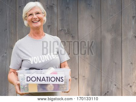 Portrait of smiling female volunteer holding donations box against wooden background