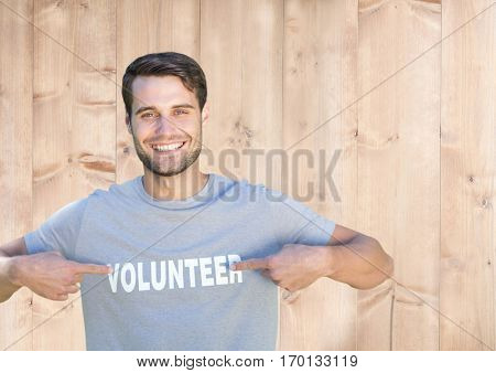 Portrait of smiling man pointing at volunteer title on his tshirt against wooden background
