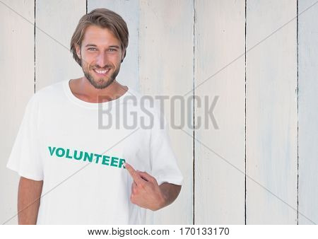 Portrait of smiling man pointing at message printed on their tshirt against wooden background