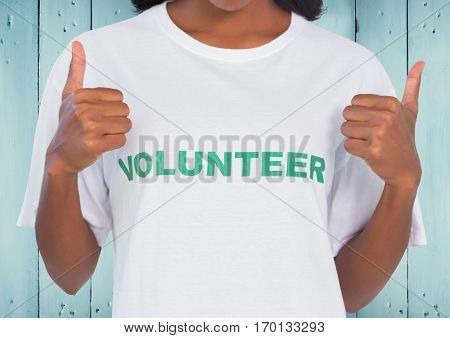 Mid-section of female volunteer showing thumbs up against wooden background