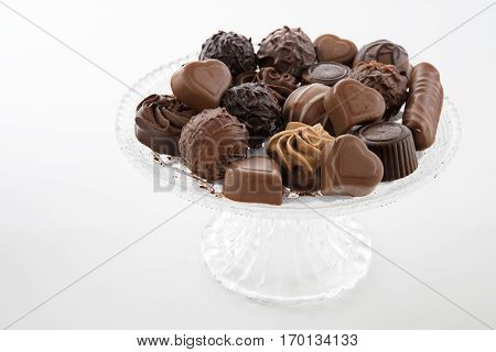 Chocolate praline assortment on a glass plate against a light gray background selected focus narrow depth of field