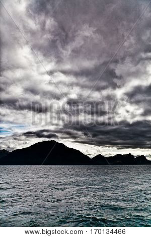 Landscape of a Fjord Norway from the sea with silhouette of mountain and dramatic grey cloudy sky