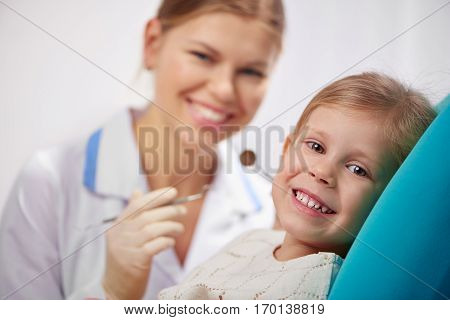 Joyful little girl having yearly checkup in dental clinic. Concept of healthy milk teeth and cavity protection.