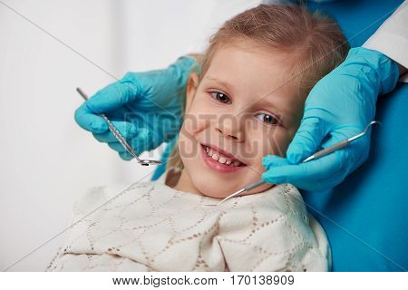 Doctor hands in gloves holding dental tools near smiling girl patient. Concept of teeth feeling and treatment.