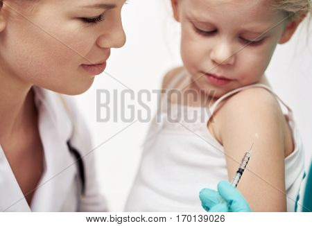 Little child having flu vaccine in hospital. Close-up of woman doctor hands in gloves holding syringe near patient's arm.