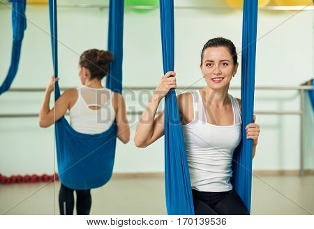 Smiling cute young woman in studio antigravity yoga