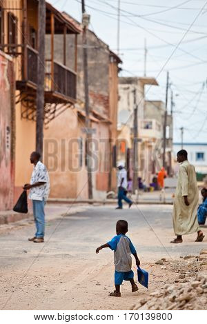 Street life with poeple walking around and a little kid, Saint Louis Senegal
