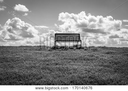 black and white isolated public bench on the top of a dyke with green grasse blue sky and white cloud
