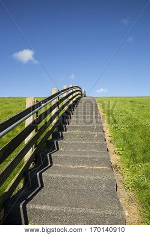 A concrete staircase with wood banister between the green grass of a dike on a sunny day
