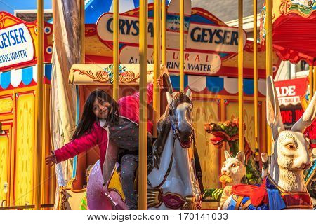 San Francisco, California, United States - August 14, 2016: closeup of smiling child rides horse of carousel at Fisherman's Wharf shopping center of Pier 39. Leisure, recreation and holidays concept.