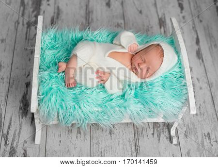 sleeping newborn boy in white romper on little bed with fluffy turquoise blanket
