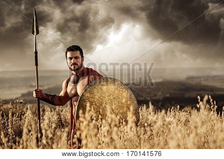 Warrior man with bare torso wearing red cloak holding sword and standing among field at dark. Male wearing like spartan or antique roman soldier going on war. Looking at camera.