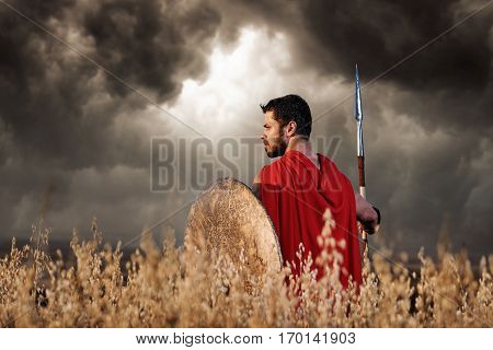 Back view of warrior wearing in red cloak like spartan or antique roman solider turned back and looking away. Brunet with beard holding sword and shield going in attack. Bad weather with dark clouds.