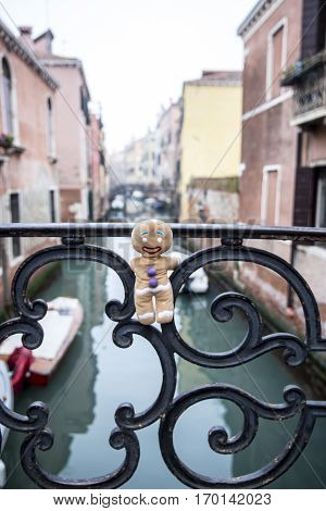 Little Gingerbread Man gingerbread man plush toy figurine visiting Venice hanging on  a bridge