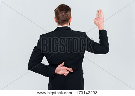 Back view of Business man in black suit lying. Holding hand with fingers crossed behind his back and swears. Isolated gray background