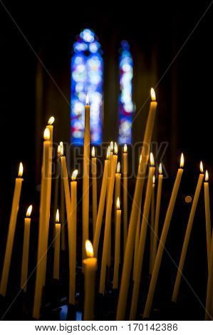 Burning candles in a church with a dark background and blue stained glass windows