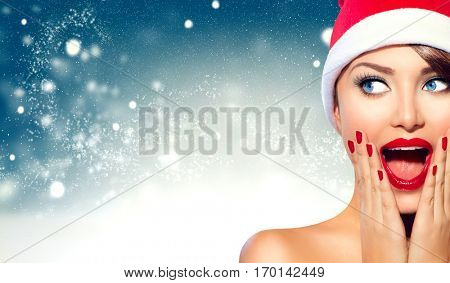 Christmas woman. Beauty model girl in Santa Claus hat with red lips and matching manicure looking right with a surprised expression. Closeup portrait over winter snow wide background with copy space
