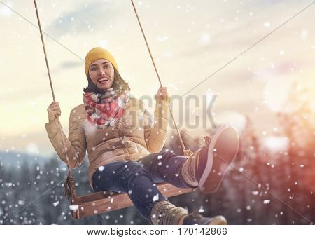 Beautiful young woman on a swing on snowy winter walk. Outdoor fun for winter vacation. Portrait girl on sunset background.