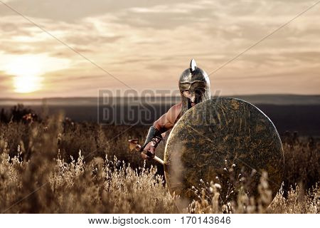 Front view of soldier like spartan in bronze helmet holding iron weapon and rounded shield looking at camera. Warrior with bare torso going forward. War in field. Dark dramatic sky ar sunset.