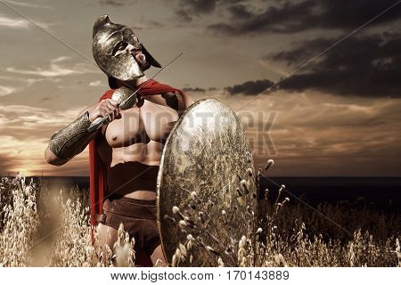 Emotionally warrior with bare torso in helmet showing to his enemy gesture of dead by weapon. Soldier in iron armor and red cloak with shield and holding sword near neck. War in field at sunset.