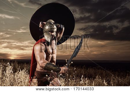 Warrior wearing in red cloak like spartan or antique roman soldier going forward in attack with iron sword. Incognito in helmet with bare torso holding bronze sword over head. Dark sky at sunset.