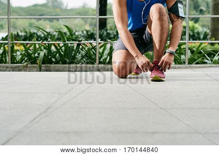 Close-up shot of sporty young man tying his shoelaces before starting daily morning run in lovely green park
