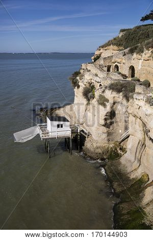 traditional fisherman's wooden hut at the bottom of the limestone cliff in the estuary of Gironde Meschers-sur-Gironde