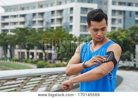 Waist-up portrait of sweaty young athlete listening to music in headphones and choosing necessary tunes for training on his smartphone