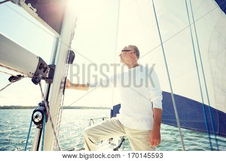 sailing, age, tourism, travel and people concept - senior man on sail boat or yacht floating in sea
