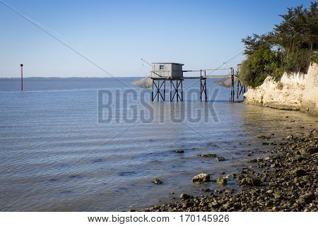 traditional fisherman's wooden hut by a limestone cliff in the estuary of Gironde, Talmont, France