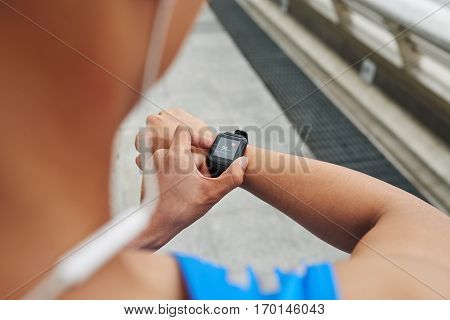 Close-up shot of young sportsman in blue T-shirt checking his heart rate on fitness tracker, over the shoulder view