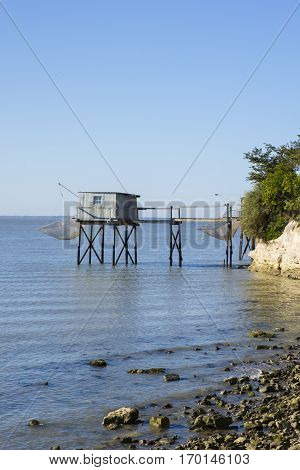 traditional fisherman's wooden hut at the bottom of the limestone cliff in the estuary of Gironde, Talmont, France