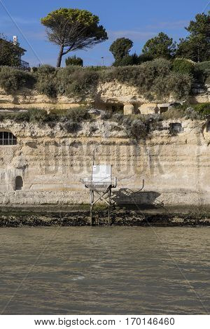 View from the Gironde estuary with the limestone cliff of the village of Meschers sur Gironde and its troglodytic houses and traditionnal typical wooden fisherman cabin Charente maritime France