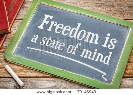 freedom is a state of mind - inspirational text on a  slate blackboard with a white chalk and a stack of books against rustic wooden table