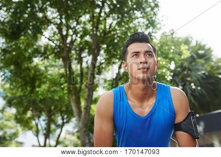 Waist-up portrait of sweaty Asian athlete with smartphone and headphones relaxing after energy-sapping marathon
