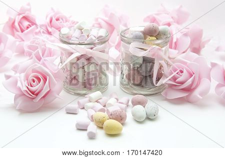 Easter Treats with mini eggs pink roses and Marshmallows on a white background