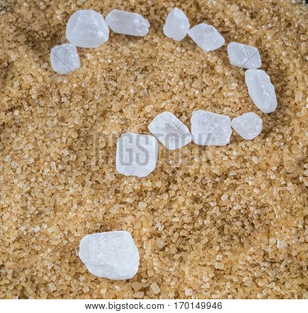 The question mark written with crystalline sugar (candy) white into a pile of brown sugar crystal Demerara.