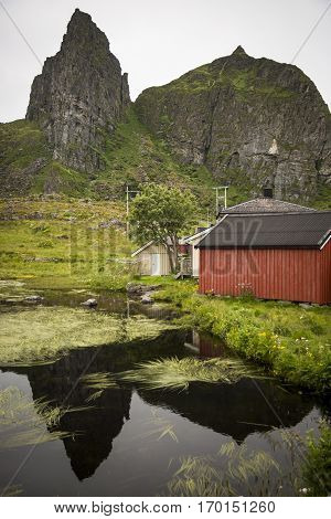 Norwegian landscape: red wooden house with a mountain and a lake view of Sanna Island