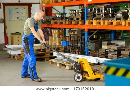 Worker In Factory With Hand Lift